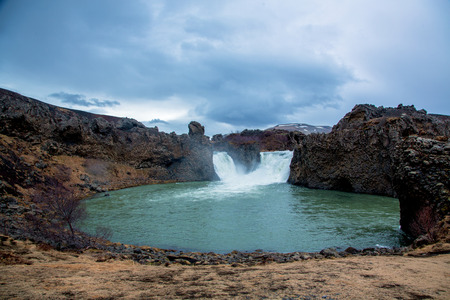 Green waterfall with basalt rock in beautiful icelandic nature Stockfoto - 124810324