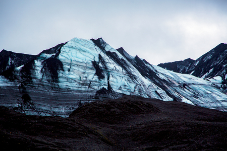 Impressive blue-black glacier wall with ash sand in the foreground in gray sky Stockfoto - 124810332