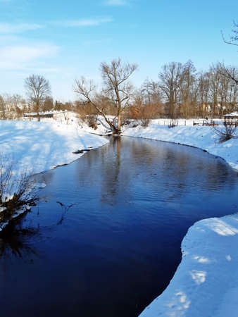 the river has a deep blue sky on both banks of the river is white snow