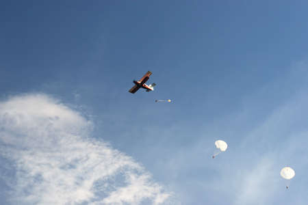 pilotage: paratroopers jump from biplane in sky Stock Photo