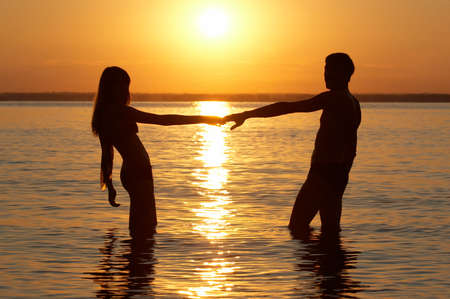 man and woman in water hold each other hand Stock Photo