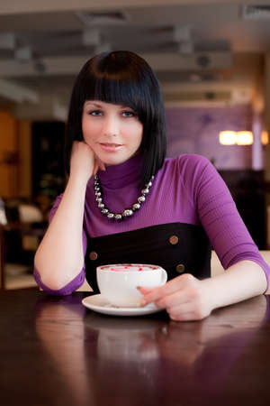 girl hold cup of coffee in hand looking straight Stock Photo
