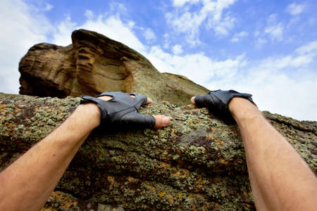 struggling: hands of rock climbing man Stock Photo