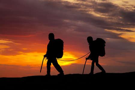 rockclimber: silhouette of two walking rock climbers on sunset sky