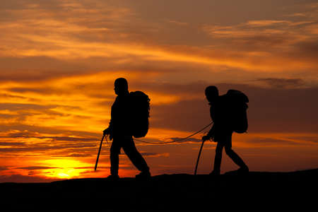struggling: silhouette of two walking rock climbers on sunset sky
