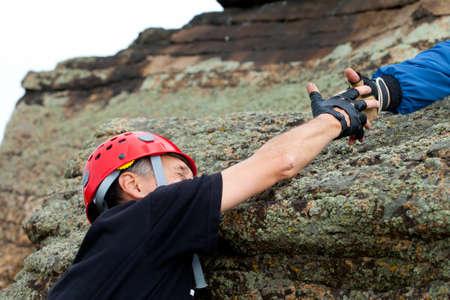 escalador de roca toma la mano de amigo