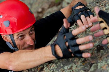 confianza: escalador de roca toma la mano de amigo
