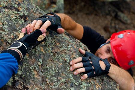 rock climber take hand of friend photo