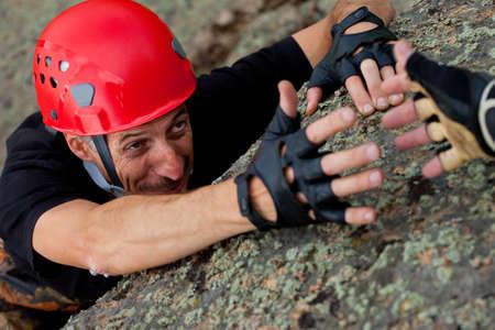 rock climber take hand of friend