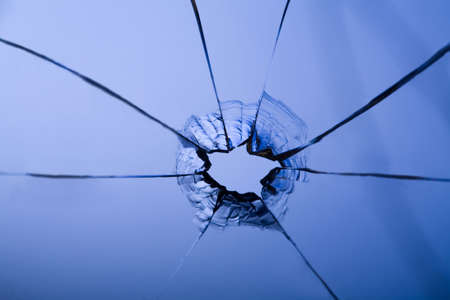 broken glass: bullet hole in glass on blue with crack Stock Photo