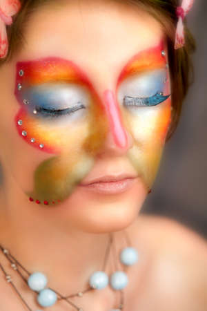 girl with butterfly make-up on face close eyes photo