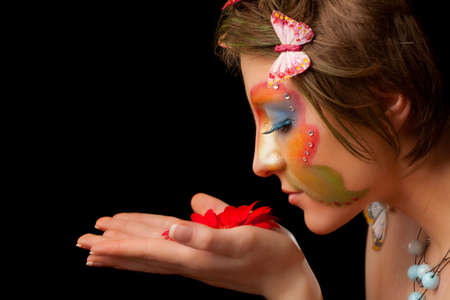 girl with butterfly make-up on face look on flower Stock Photo