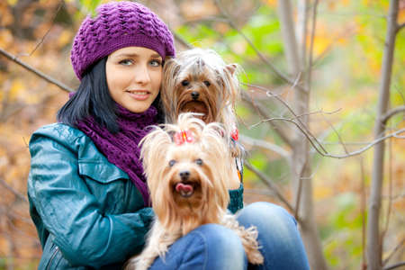 girl is sitting with two small dogs photo