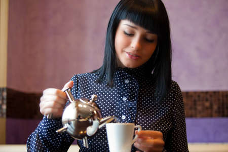 woman in cafe filling cup with teapot photo