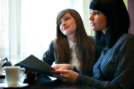 two women in cafe reading menu Stock Photo