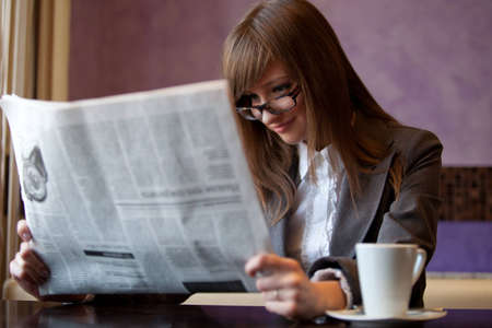 business woman in cafe read newspaper photo
