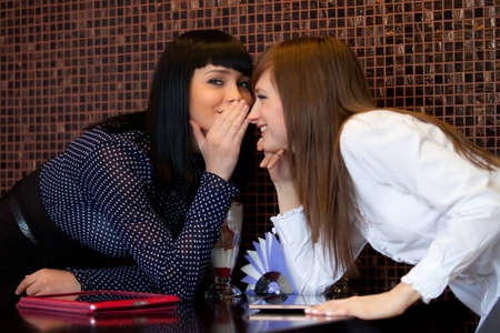 one woman whisper something to friend photo