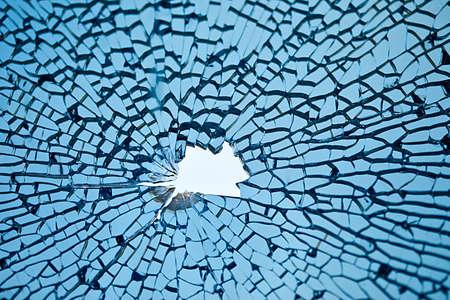rompiendo: de vidrio azul con muchas grietas y agujeros en la media Foto de archivo