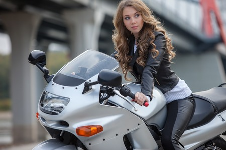woman in black sitting on motorcycle
