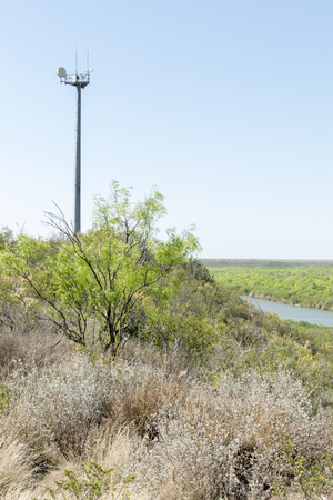A United States Border Patrol camera tower watches over the Rio Grande river in the spring time which is an area of drug smuggling and illegal alien smuggling. On the other side of the river is Mexico.
