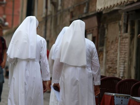 Three Catholic nuns in white habits about to cross a Venice       Banque d'images
