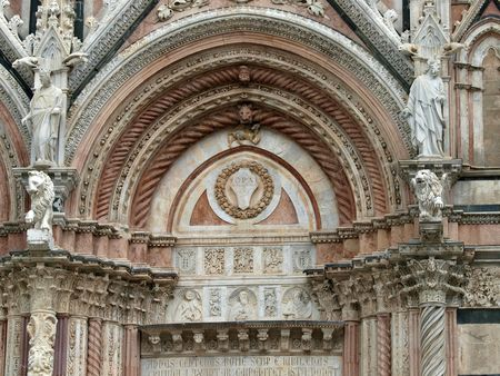 Siena - marble Duomo portal. The Duomo of Siena, which was built in the 12th and 13th centuries, is one of the prettiest churches in Gothic style in Italy photo