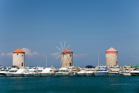 Medieval windmills at Mandraki Harbour in the Dodecanese island of Rhodes, Greece.