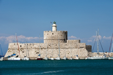 Medieval fortress of Saint Nicholas, now the site of a lighthouse, in Mandraki Harbour, Rhodes New Town, Greece.