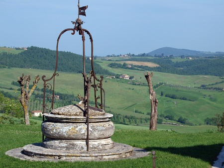 old well on the background of the Tuscan landscape photo
