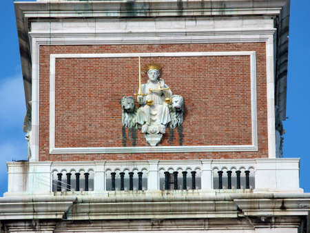 Venice - Justice between the Venetian lions on the facade of the tower of St Marks photo