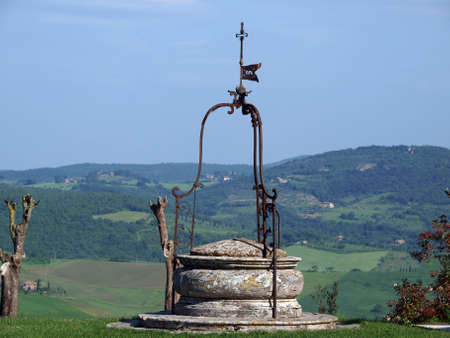 sant'antimo: old well on the background of the Tuscan landscape
