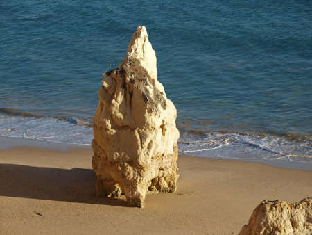 vilamoura: A lonely rock in the ocean. The effect of erosion Stock Photo