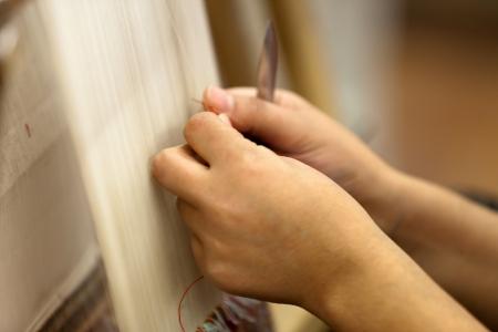 the Turkish woman knitting the silk carpet photo