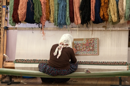 rug weaving: the Turkish woman knitting the silk carpet Editorial