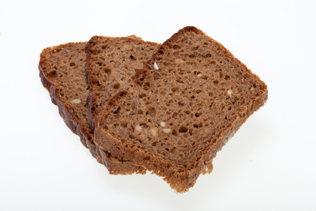 Slices of dark bread isolated over white  photo
