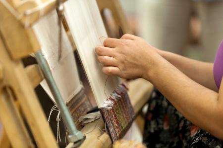 the Turkish woman knitting the silk carpet Archivio Fotografico