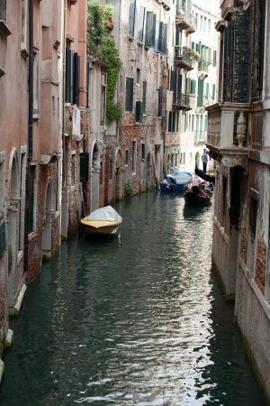 Narrow canal with gondolas in Venice, Italy  photo