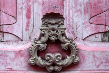 Door knoker on an old pink  wodden door photo