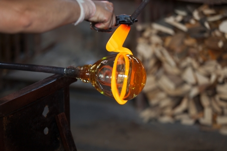 glass blower carefully making his product  photo