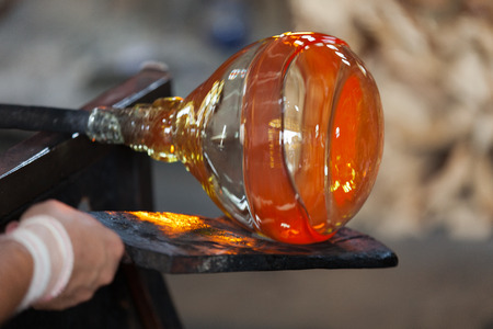 glass vase: glass blower carefully making his product