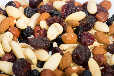 mixed nuts and dried fruits isolated on white background photo