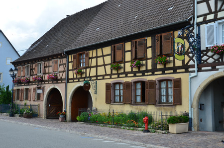 Street with half-timbered medieval houses in Eguisheim village along the famous wine route in Alsace, France  photo