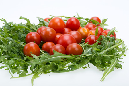 ruccola: Heap of ruccola leaves and cherry tomatoes Stock Photo