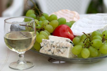 tabla de quesos: Varios tipos de queso, uvas y un vaso de vino blanco