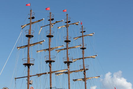Masts and sails of huge sailing boat against the background\ of blue sky