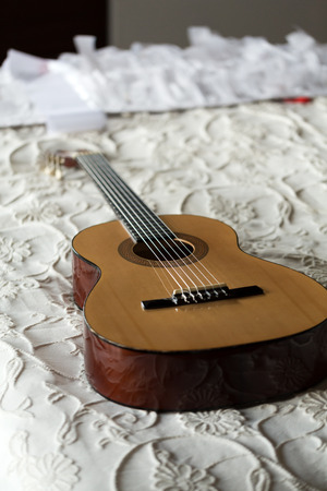 Spanish guitar lying on the bed photo