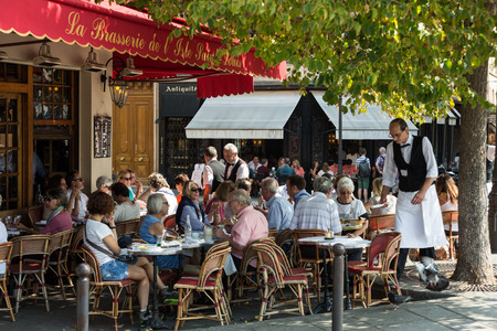 Paris, France - September 9, 2014: : People visit Brasserie de l'Isle Saint-Louis on September 9 2014 in Paris. This is the typical Parisian café Zdjęcie Seryjne - 33860101