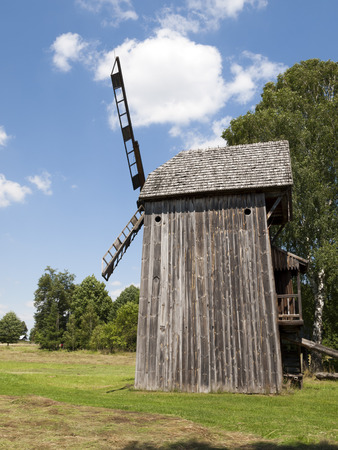 Old wooden windmill on background of blue sky photo