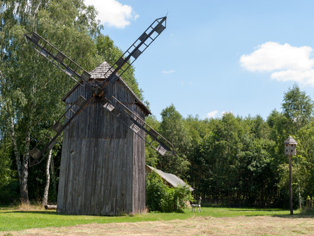 ethnographic: Old wooden windmill on background of blue sky