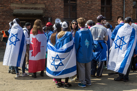 nazi flag: OSWIECIM, POLAND - APRIL 16, 2015:   International Holocaust Remembrance Day . Annually people from the all the world meets on the March of the Living in german Concentration Camp in Auschwitz Birkenau. Poland